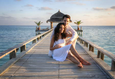 happy smiling: Happy loving couple in white clothes posing on a pier on Maldives