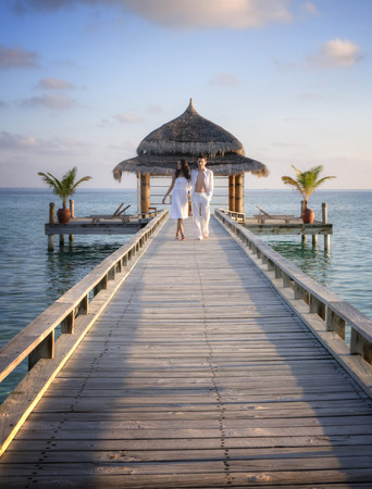 Glückliche liebevolle Paare in der weißen Kleidung, die auf einem Pier auf den Malediven Standard-Bild