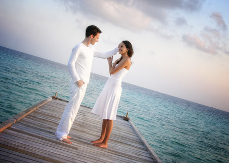 jetty: Happy loving couple in white clothes posing on a pier on Maldives