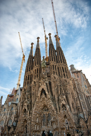 spires: Exterior view of the ornate spires of the Familia Sagrada, Barcelona, Spain with industrial cranes, a historic landmark Roman Catholic Church still under construction, view looking up Editorial