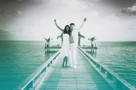 love couple: Sensual love couple on a jetty on Maldives. Grayscale picture with azure color accent. Stock Photo