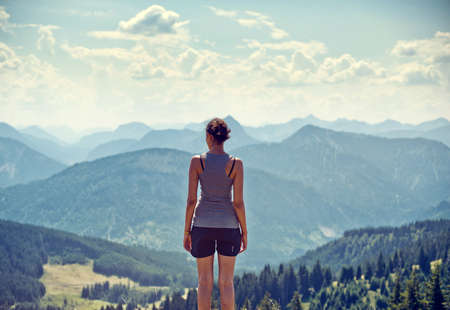 Young woman hiker standing admiring a mountaintop view looking out over distant ranges of mountains and valleys in a healthy active lifestyle concept Stock Photo - 44592478