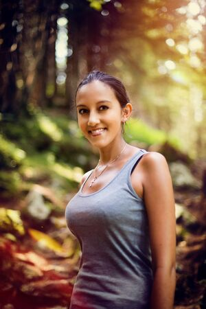 tetona: Atractiva feliz disfruta de la naturaleza Mujer india joven de pie en un bosque de montaña bañada por el cálido resplandor de la puesta del sol de verano, el concepto de estilo de vida sana al aire libre Foto de archivo