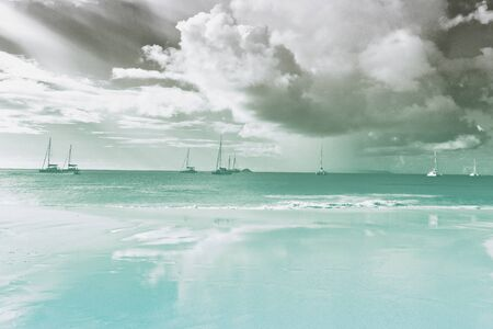 cloud formations: Scenic cloud formations over Anse Lazio Beach, Praslin, Seychelles with boats on the ocean in the background Stock Photo