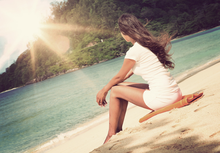 Young woman enjoying a seaside sunrise sitting barefoot on a tropical beach facing into the rising sun with her hair blowing in the breeze, view from the rear