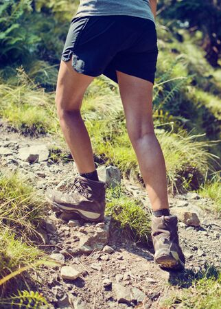 hillwalking: Young woman wearing sturdy hiking boots climbing up a rocky mountain footpath in a health and fitness concept, close up view of her legs