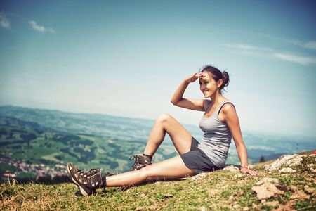 Young woman hiker sitting on a mountain ridge taking a rest and looking into the distance at the surrounding view with her hand raised to her forehead shading her eyes, profile view on the skyline