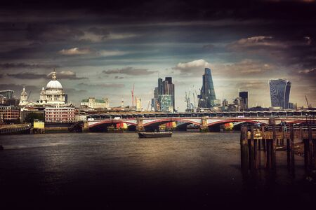atmospheric: Artistic dark atmospheric view of London city skyline and a bridge over the River Thames with St Pauls Cathedral in a shaft of light, travel concept