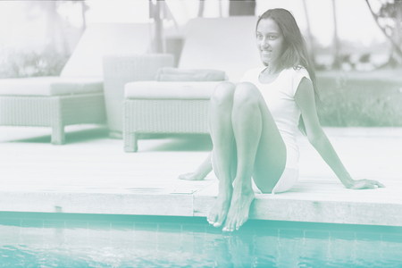 swimming shorts: Pretty Smiling Young Woman in White Shirt and Shorts Sitting at the Swimming Pool Edge. Stock Photo