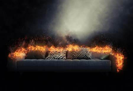 burning: Large generic three-seater sofa engulfed in burning flames in a smoky dark atmosphere with a beam of light shining on it and copyspace