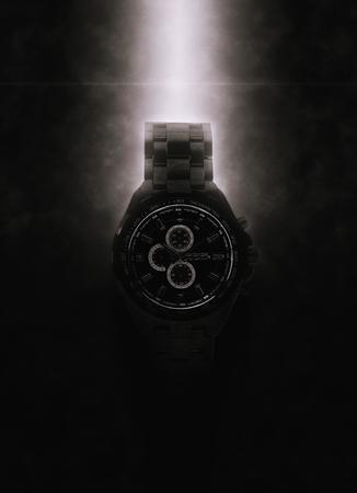 dramatically: Luxury Design Black Wristwatch Lit Dramatically from Above on Dark Background Stock Photo