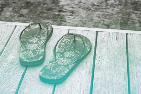 printed: Decorative floral slip slops on a wooden pool deck overlooking the mottled blue-green water Stock Photo