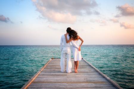 モルディブの桟橋でお互いを保持して白い服で官能的な愛のカップル。