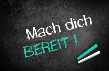 get ready: Conceptual Get Ready Message in German Texts Written on Black Chalkboard with Two Chalks in Lower Right Corner.