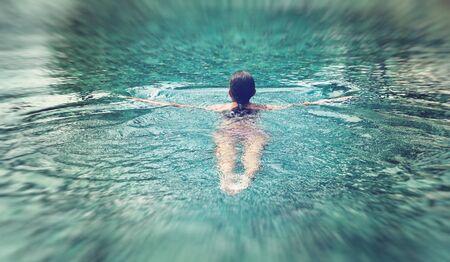 invitando: Natación de la mujer lejos de la cámara en un acogedor fresco espumoso piscina azul disfrutando el clima cálido verano Foto de archivo