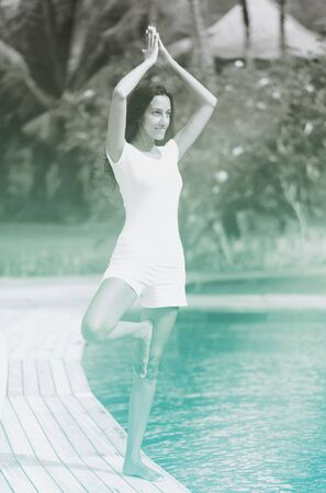 enhanced healthy: Slim woman doing a yoga pose next to a cool pool. Grayscale image with azure color accent. 3d Rendering.