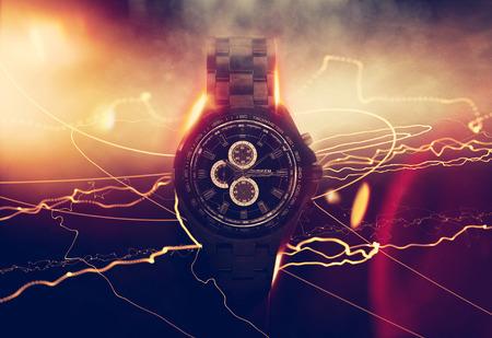iluminado a contraluz: Luxury Design Negro Reloj Cronógrafo dramáticamente iluminado de lado sobre fondo oscuro con efecto brillante, destellos de lente y rayos de luz