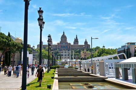historical landmark: External frontal view of the National Museum of Catalan Art, Barcelona, Spain, a historical cultural landmark, with tourists walking up the walkway at the side