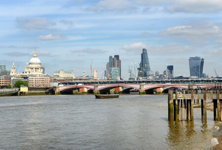 st   pauls cathedral: Bridge across the River Thames, London with a view of the city skyline and St Pauls Cathedral behind with an old wooden jetty in the foreground