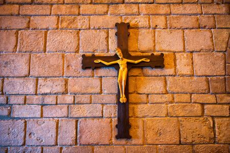 sacred trinity: Artistic crucifix with the representation of Jesus Christ crucified on a wooden cross, mounted on an old stone block wall