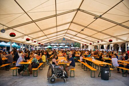 undercover: View of a Bavarian styled Oktoberfest in Barcelona, Spain taking place in an undercover marquis with rows of benches and people and a wheelchair in the foreground