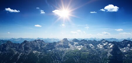 landscape: Mountainous scenic panoramic landscape with the sun shining bright over the Alps, at the border between Germany and Austria Stock Photo