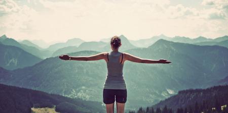 Frau natur feiern und erreichen den Gipfel eines hohen Berges, als sie steht mit dem Rücken zur Kamera und gestreckten Armen aus, die über Bergketten und Täler in einer Panorama-Landschaft Standard-Bild