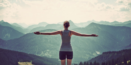 zen: Woman celebrating nature and reaching the summit of a high mountain as she stands with her back to the camera and arms extended looking out over mountain ranges and valleys in a panoramic landscape
