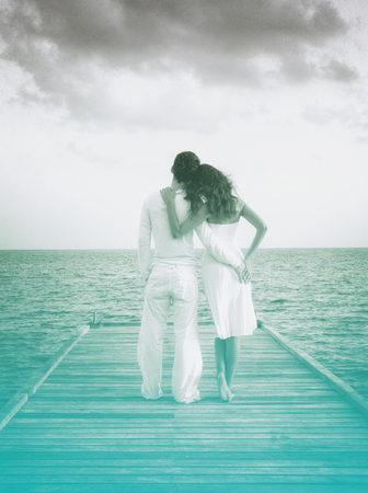 sexual intimacy: Sensual love couple on a jetty on Maldives. Grayscale picture with azure color accent. Stock Photo