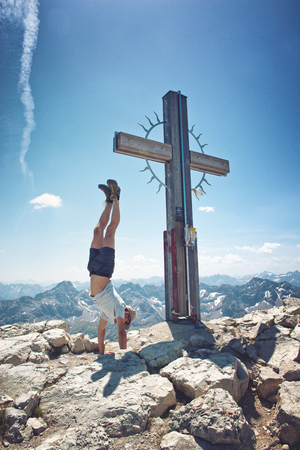 handstand: Hiker doing a handstand on the peak  summit of the Hochvogel mountain in the Alps, Germany Stock Photo