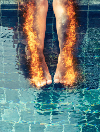 consumed: Woman with burning legs consumed in fiery orange flames and scorched skin dangling her legs over a swimming pool Stock Photo