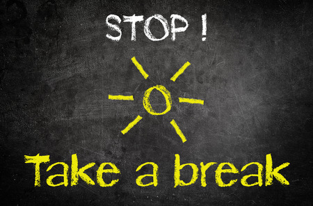 take a break: Conceptual Stop and Take a Break Message Written on a Black Chalkboard with Yellow Sun Drawing in the Middle.