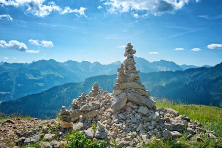 rock formations: Manmade Cairn Rock Structures Overlooking Picturesque Mountain Range on Bright Sunny Day with Blue Sky