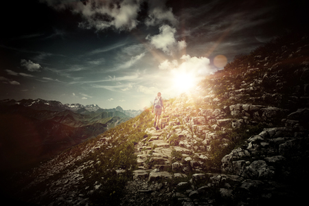 Rear View of Female Hiker Ascending Precarious Trail on Side of Rocky Mountain Heading Toward Bright Dramatic Sunlight with Vignette Effect - Concept Image Illustrating Inspiration and Aspiration Stock Photo