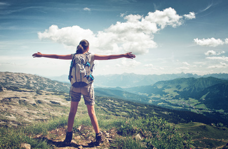 arm extended: Rear View of Female Hiker Wearing Backpack Standing with Arms Open on Summit of Mountain Overlooking Lush Green Valley, Freedom Concept Image