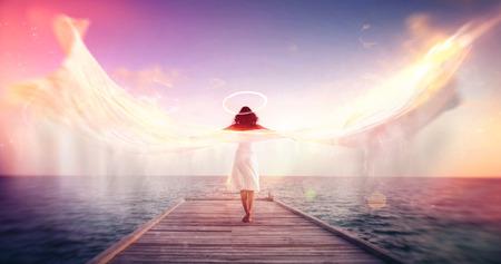 후광과 화려한 태양 효과 플레어와 모션 블러와 화이트 패브릭을 쏜다의 형태로 날개를 가진 바다가 내려다 보이는 부두에 맨발로 서있는 여성 천사,