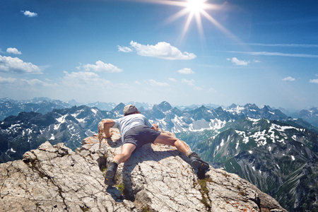 Mountain climber looking over the edge of the summit of an alpine peak lying on his stomach on the rock with distant snow-capped peaks stretching away into the distance, sunburst above Stock Photo