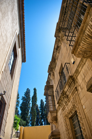 blue facades sky: Low Angle View of Historical Building Facades of Poble Espanyol Museum Area - Looking Up at Architectural Detail, Blue Sky and Tall Trees, Barcelona, Spain Editorial