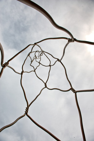 Low Angle View of Abstract Wire Street Art Sculpture in Barcelona, Spain Backlit by Overcast Sky with Sun Peeking Through Editorial