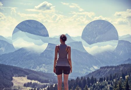 clairvoyance: Rear View of Young Woman Standing in Alpine Region Admiring View of Mountains and Valley on Sunny Day Framed by Double Upside Down Spheres