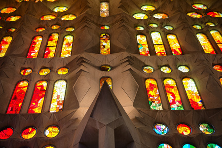 tourist attraction: Architectural Interior View of Sagrada Familia Church in Barcelona, Spain - Looking Up at Colorful Stained Glass Glowing in Exterior Sunlight