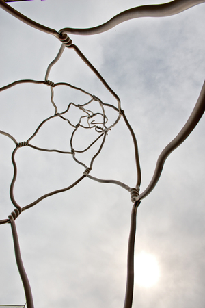 coercion: Low Angle View of Abstract Wire Street Art Sculpture in Barcelona, Spain Backlit by Overcast Sky with Sun Peeking Through Editorial