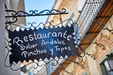 culinary tourism: Hand painted ornate restaurant sign haning from an exterior wall bracket in Espanyol Poble, Barcelona, Spain.an architectural museum area