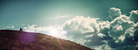 ? ?  ? �silence: Panor�mica de Solitary persona sienta solamente en la colina que mira la salida del sol brillante en el cielo azul nublado - Concepto Imagen Foto de archivo