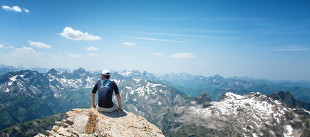 Man Sitting on Rock Ledge Enjoying the View and Serenity of Allgau Alps Mountain Ranges on Sunny Day with Blue Sky Stock Photo