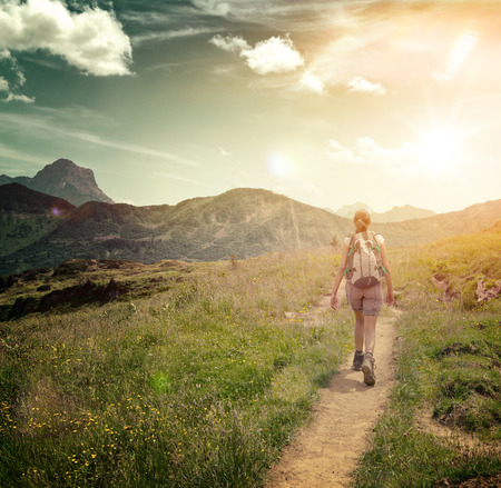Rear View of Woman Hiking Along Remote Green Valley Trail Towards Bright Sun and Mountain Landscape
