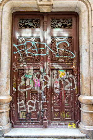 unsightly: Graffiti scrawled across the surface and panels of on an old ornate wooden carved door in a stone surround in Barcelona , Spain damaged by vandals