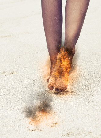 burning: Woman with her burning feet aflame and black scorch marks on her legs and feet over a textured neutral background with reflection in a healthcare and injury concept