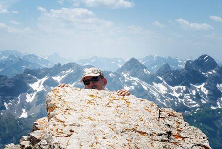 allgau: Man Wearing Hat and Sunglasses Peeking Over Edge of Mountain Ledge at Camera in Allgau Alps Near German-Austrian Border Stock Photo