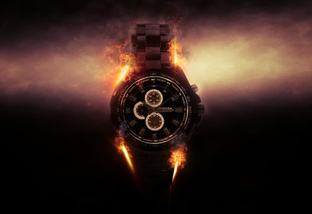 Luxury Design Black Wristwatch Chronograph Lit Dramatically from Side on Dark Background with Glowing Effect and Flames Stockfoto